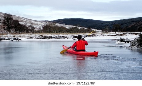 Kayaking through ice on the River Brora in the Highlands of Scotland in winter
