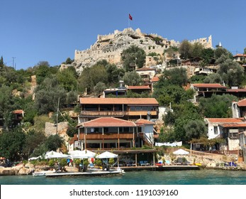 Kayakoy Kekova(Simena) village,Fethiye,Mugla Sunken city of Kekova in bay of Ucagiz view from sea in Antalya province of Turkey with turqouise sea rocks and green bushes with remains of ancient city