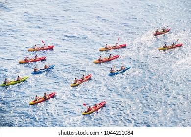 Kayaks. Big group of people kanoeing in the sea. People kayaking in the ocean.