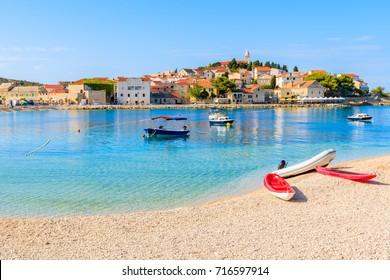 Kayaks and boats on beach in Primosten town, Dalmatia, Croatia