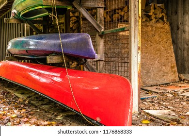 kayaks and canoe stacked in stand by the cottage shed in early fall.