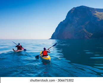 Kayaks. Couple kanoeing in the sea near the island with mountains. People kayaking in the ocean.