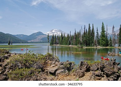 kayaks in front of beautiful mountain peaks in central oregon on a peaceful lake