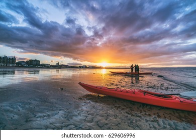 Kayaks and kayakers on beach at sunset. Portobello, Edinburgh, Scotland, UK