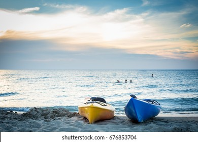 Kayaks on the beach at sunset with paddlers swimming in the background