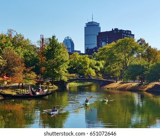 Kayaks on the Charles River Esplanade in Boston Massachusetts lined with trees, a bridge across the water and city buildings in the background on a beautiful clear blue sky autumn day.