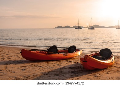 Kayaks on sandy beach during sunset. Travelling and sabbatical.