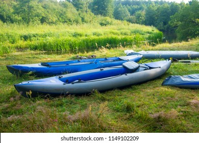 Kayaks for rafting along the river on the river bank. Boats or canoes on the river shore