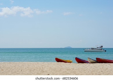 Kayaks are waiting for tourist on the Pattaya beach in sunny day. The yacht is in the blue ocean in the bright day. Space for copy.