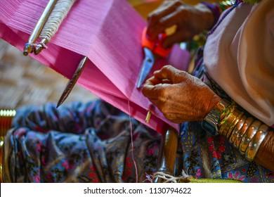 A Kayan woman (Long Neck People) weaving silk fabric on a wooden loom in Inle Lake, Myanmar.