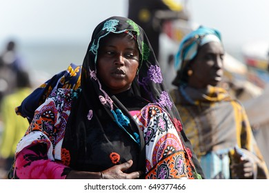KAYAR, SENEGAL - APR 27, 2017: Unidentified Senegalese woman in colored clothes and headscarf stands on the coast of the Atlantic Ocean. Many Kayar people work in port