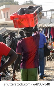 KAYAR, SENEGAL - APR 27, 2017: Unidentified Senegalese man walks with a box on his head on the coast of the Atlantic Ocean. Many Kayar people work in port