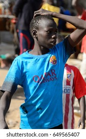 KAYAR, SENEGAL - APR 27, 2017: Unidentified Senegalese little boy puts a hand on his head on the coast of the Atlantic Ocean. Many Kayar people work in port