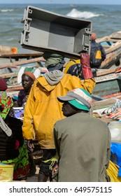 KAYAR, SENEGAL - APR 27, 2017: Unidentified Senegalese man carries a box on the coast of the Atlantic Ocean. Many Kayar people work in port