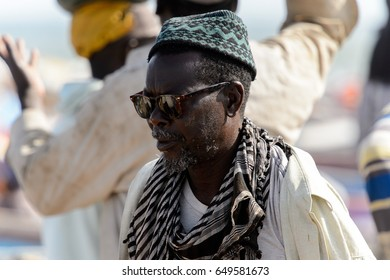 KAYAR, SENEGAL - APR 27, 2017: Unidentified Senegalese man in sunglasses and a hat walks on the coast of the Atlantic Ocean. Many Kayar people work in port