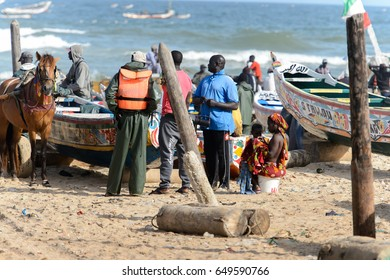 KAYAR, SENEGAL - APR 27, 2017: Unidentified Senegalese people stand among the boats on the coast of the Atlantic Ocean. Many Kayar people work in port