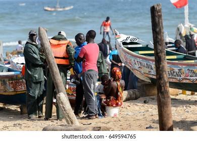 KAYAR, SENEGAL - APR 27, 2017: Unidentified Senegalese people talk about something on the coast of the Atlantic Ocean. Many Kayar people work in port