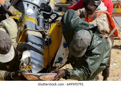 KAYAR, SENEGAL - APR 27, 2017: Unidentified Senegalese man pulls a boat out from the water on the coast of the Atlantic Ocean. Many Kayar people work in port