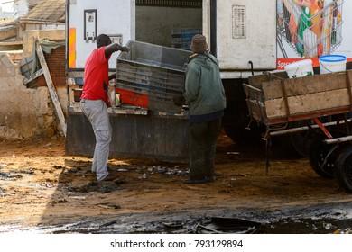 KAYAR, SENEGAL - APR 27, 2017: Unidentified Senegalese two men put the box into the truck in the street of Kayar, Senegal.