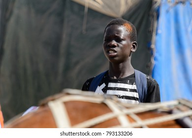 KAYAR, SENEGAL - APR 27, 2017: Unidentified Senegalese boy in black shirt with white stripes frowns at the local market of Kayar, Senegal.