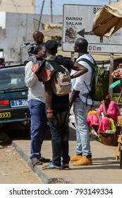 KAYAR, SENEGAL - APR 27, 2017: Unidentified Senegalese people talk about something beside the road at the local market of Kayar, Senegal.