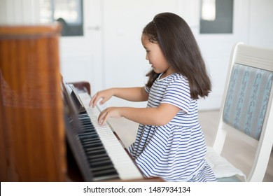 Kazakh asian little girl learning to play piano