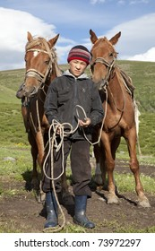 Kazakh boy holds the reins of two horses in the pasture