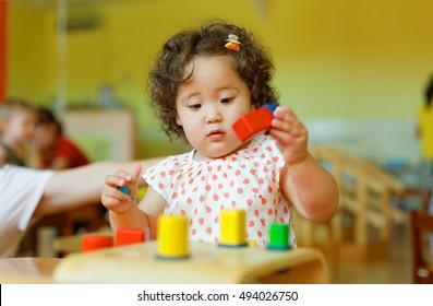 kazakh curly girl playing in kids development center
