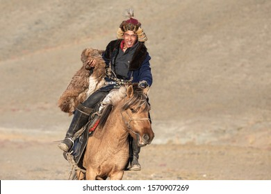 Kazakh eagle hunters partaking in a traditional wrestling match. Two wrestlers on horseback start pulling on a sheep skin, the one who retrieves it, is the winner. Ulgii, Mongolia.