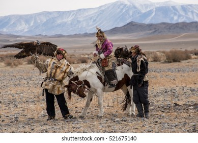 Kazakh Eagle Hunters in traditionally wearing typical Mongolian dress culture of Mongolia she Rider horse on Altai Mountain background  at Ba-yan UlGII, MONGOLIA