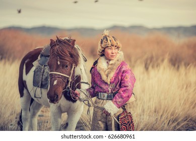 Kazakh Girl Eagle Hunters in traditionally wearing typical Mongolian dress culture of Mongolia she Rider horse on Altai Mountain background at Ba-yan UlGII, MONGOLIA