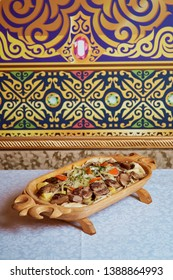 Kazakh national dish beshbarmak on a traditional background in a wooden plate
