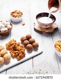 Kazakh national food like zhent, kurt, milk, sweet balls from cottage cheese, nuts and raisins during Nauryz festival on white wooden background.
