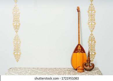 Kazakh national musical instrument dombra on a white background. National Kazakh decor gold ornaments and household items. Kazakh Kyrgyz ethnic background