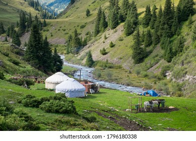 Kazakh traditional nomad's yurts on beautiful mountain meadows in the green Tien Shan Mountains in Tekes area in the summer. Rich unique nature of Central Asia.