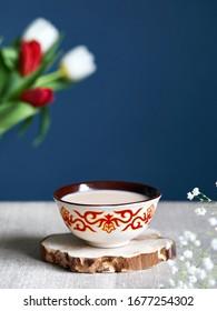Kazakh traditional tea bowl kese with black tea and milk inside near tulips at dark blue background during Nauryz festival.