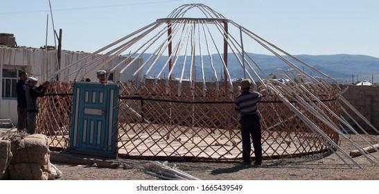 Kazakhs setting up the skeleton of a yurt