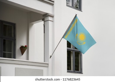Kazakhstan flag. Kazakhstan flag hanging on a pole in front of the house. National flag waving on a home displaying on a pole on a front door of a building. Flag raised at a full staff.