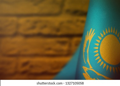 Kazakhstan hanging flag for honour of veterans day or memorial day on orange blurred painted brick wall background. Kazakhstan glory to the heroes of war concept.