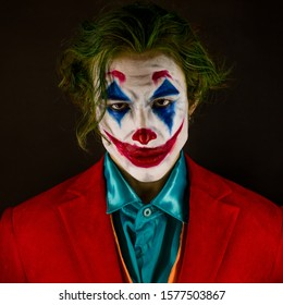 KAZAKHSTAN, KOSTANAY - OCTOBER 21, 2019: Man impersonating the Joker. Portrait of a man in a suit with clown makeup and green hair. Joker cosplay.