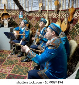 Kazakhstan, Petropavlovsk - March 22, 2018: Young people in national costumes on the national holiday Nauryz play Kazakh musical instruments in a yurt in the city park of culture and recreation