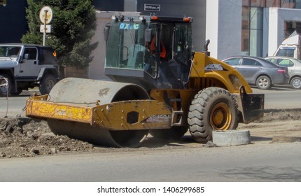 Kazakhstan, Ust-Kamenogorsk, april 23, 2019: Steamroller performing leveling work on a road under construction. Equipment for construction and repair roads. Yellow steamroller on the street