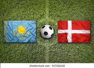 Kazakhstan vs. Denmark flags on a green soccer field