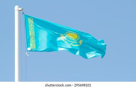 Kazakhstan waving flag against blue sky