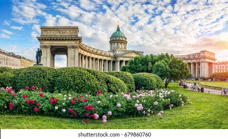 Kazan Cathedral in St. Petersburg under a blue sky with clouds and beautiful red and white peonies in front of him