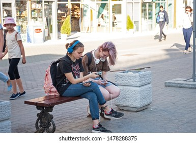 Kazan, Republic of Tatarstan, Russia - July 19, 2019. Bauman street, pedestrian street, favorite place for tourists and visitors to walk. People young girl are sitting on bench