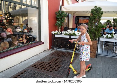 Kazan, Republic of Tatarstan, Russia - July 19, 2019. Bauman street, pedestrian street, favorite place for tourists and visitors to walk. Girl at the shop window.