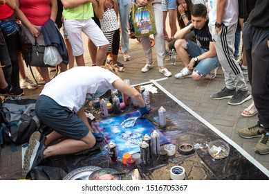 Kazan, Republic of Tatarstan, Russia - July 19, 2019. Bauman street, pedestrian street, A young man, an artist, surrounded by tourists, paints his paintings.