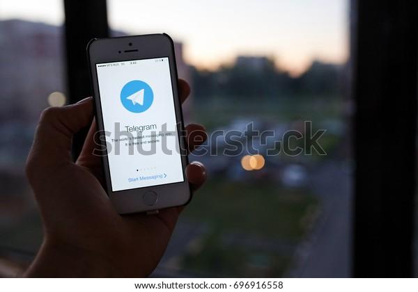 Kazan Russia 07.08.2016: iphone 5s with telegram messenger logo on screen, window on background. Illustrative editorial