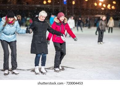 KAZAN, RUSSIA, 22 JANUARY, 2017: Three women on skating rink in the evening